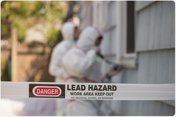 Two house painters in hazmat suits removing lead paint from an old house. Image Copyright: Jamie Hooper / Shutterstock