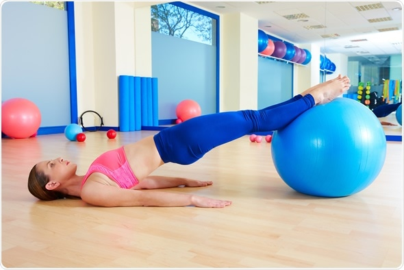 Pilates woman pelvic lift fitball exercise - Image Copyright: holbox / Shutterstock