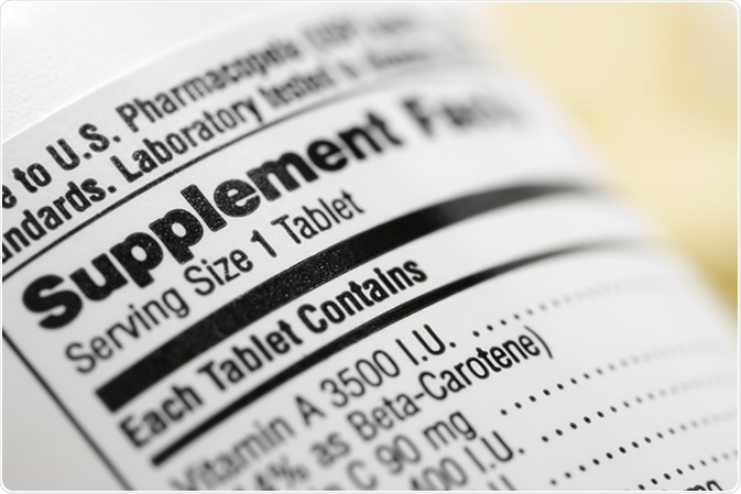 Closeup of a dietary supplement label listing the vitamins contained within each tablet. Image Credit: iofoto / Shutterstock