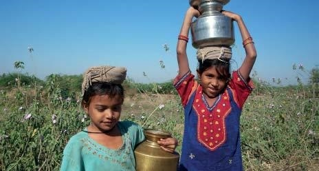 Two Indian girls carry well water to their homes. While the construction of wells in the Ganges Delta region has reduced diseases caused by pathogen-contaminated surface water, a large number of these wells produce water that is strongly contaminated with arsenic. Chronic and acute arsenic poisoning that affect large parts of the population are the consequence.