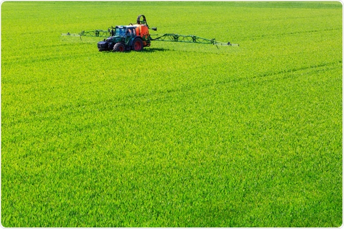 Tractor spraying glyphosate pesticides on a crop. Image Credit: GerDuess / Shutterstock