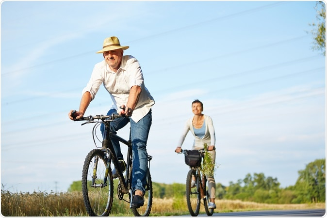 Senior couple cycling with bikes in nature in summer. Image Credit: Robert Kneschke / Shutterstock