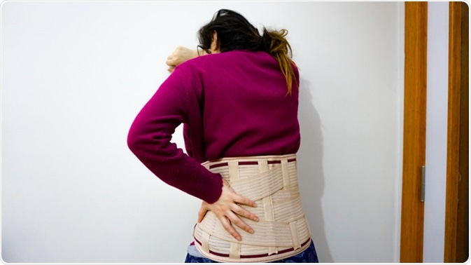 Woman with girdle for back pain. Image Credit: Akin Ozcan / Shutterstock