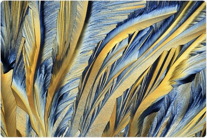Photo through a microscope of crystals growing from the melt of sulfur. Polarized light technology. Image Credit: alex7370 / Shutterstock