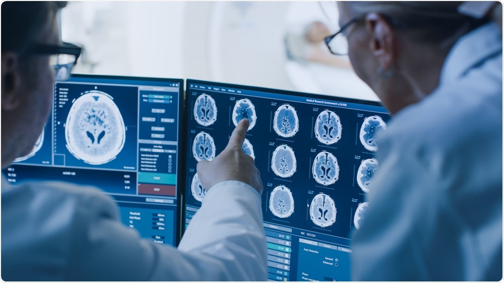 Doctors looking at MRI scan of patient with potential brain cancer.