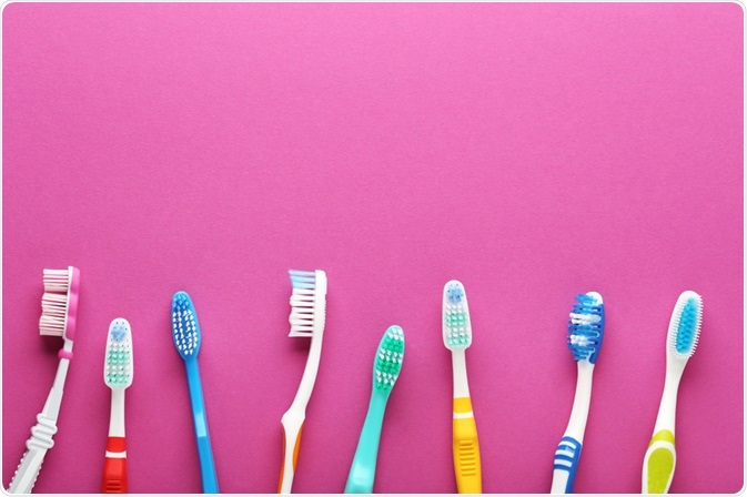 Picture of various types of toothbrushes in a line, on a pink background - picture taken by 5 second Studio
