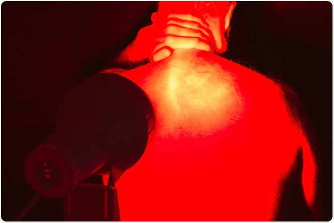 Back pain. Infrared heat light lamp therapy. Image Credit: Jaroslav Moravcik / Shutterstock