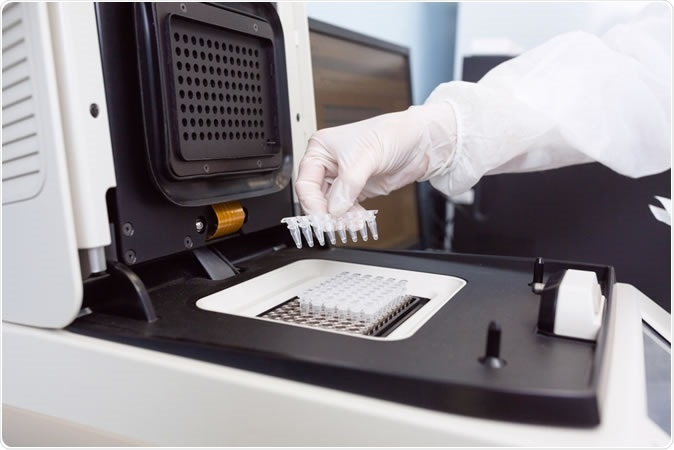 Geneticist placing strips with DNA into the PCR thermal cycler - Image Credit: UvGroup / Shutterstock