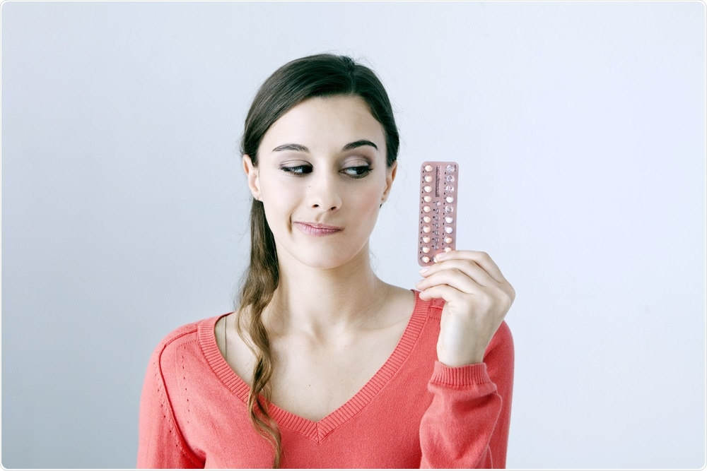 Woman holding the contraceptive pill
