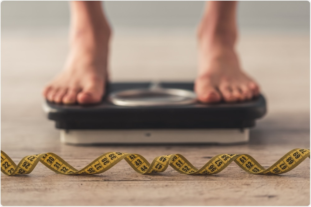 Person with an eating disorder standing on weighing scales.
