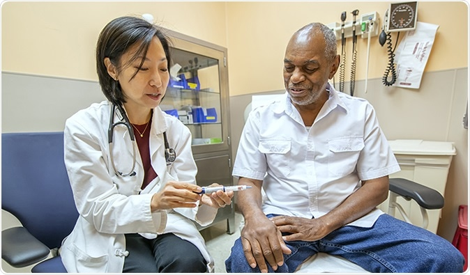 Dr. Mary Rhee, a physician-researcher with the Atlanta VA and Emory University, discusses the use of a glucometer with VA patient Joseph Fields. (Photo by Lisa Pessin)