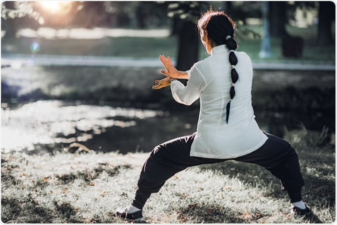 Woman practicing Tai Chi Quan in the park Credit: Microgen / Shutterstock