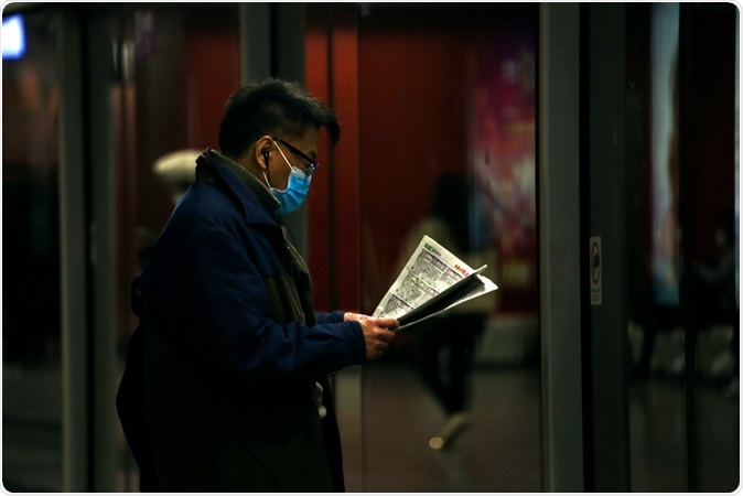 Hong Kong - January 29, 2020: A man wearing a surgical face masks reads the newspaper while waiting for the MTR. A rise in face masks followed reports of the Wuhan Coronavirus in Hong Kong. Image Credit: Katherinekycheng / Shutterstock