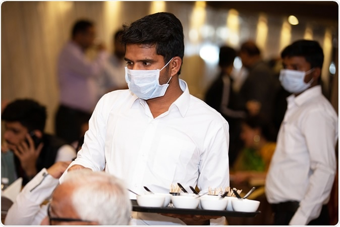 Jodhpur, Rajasthan, India - March 2020: Waiters wearing surgical masks serving food in a restaurant. Image Credit: Stockpexel / Shutterstock