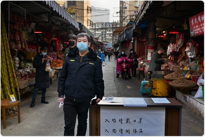 Chengdu/China-Feb.2020: A security guard with face mask outside a local wetmarket. Image Credit: Amar Shrestha / Shutterstock