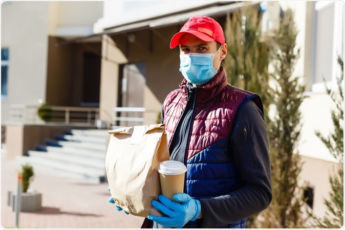 Courier in protective mask and gloves delivers takeaway food during covid-19 pandemic lockdown. Image Credit: Andrew Angelov / Shutterstock