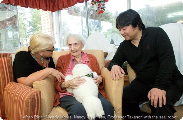 Professor Takanori is in Australia from Japan to meet with Professor Wendy Moyle to talk about the robots for dementia. At Sinnamon Park Retirement Village. L to R Wendy Moyle, Nancy Greenless, Professor Takanori with the seal robot