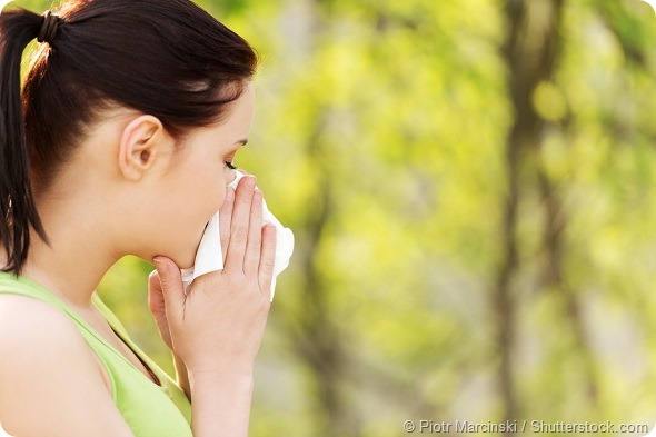 Attractive woman outdoor with tissue having allergy