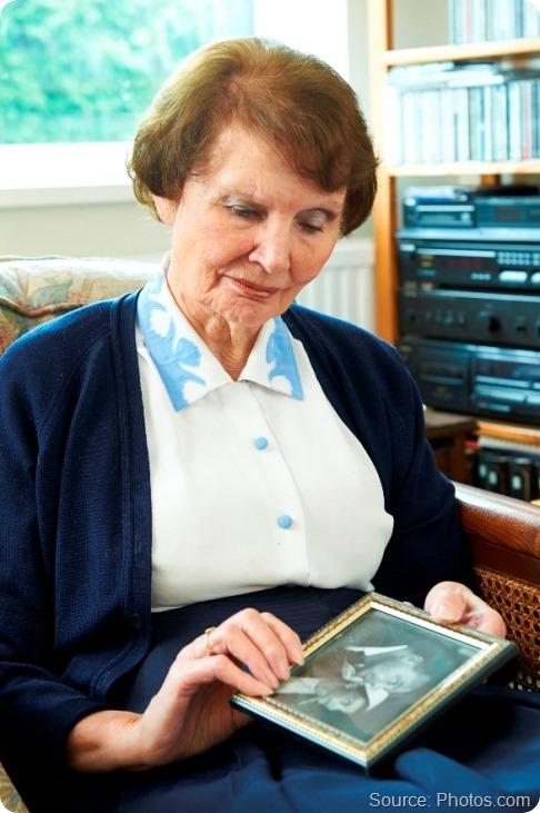 Senior Woman looking sadly at old wedding photograph