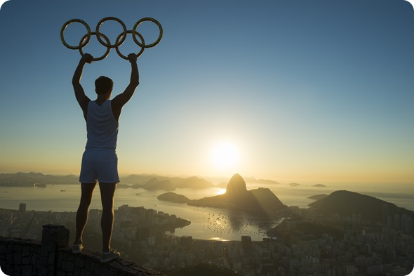 RIO DE JANEIRO, BRAZIL - MARCH 05, 2015 Illustrative editorial of man standing in silhouette holding Olympic rings above city skyline view of Sugarloaf Mountain and Guanabara Bay at sunrise-lazyllama