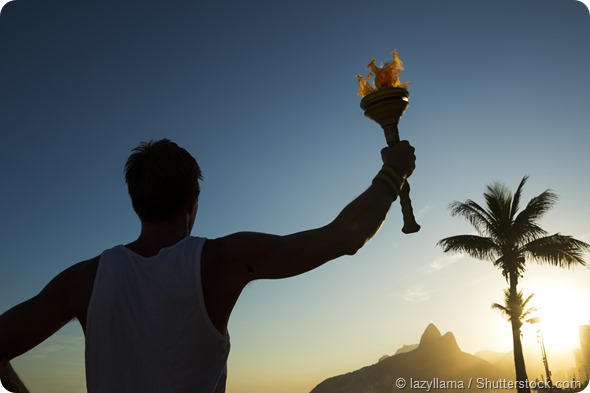 Silhouette of athlete standing with sport torch at the Rio de Janeiro Brazil sunset skyline at Ipanema Beach